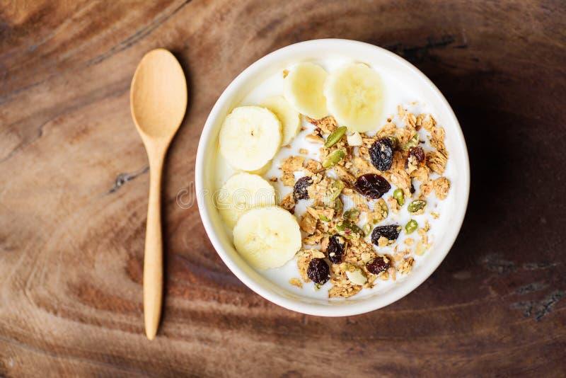 Muesli con el cereal, el plátano de la rebanada y la leche en un cuenco foto de archivo
