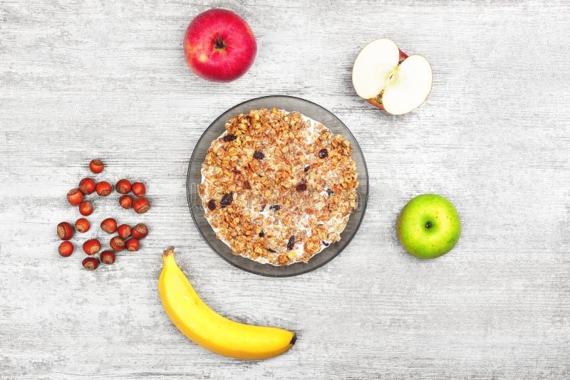 Muesli con el plátano, la manzana y las nueces Cuenco de gachas de avena con las frutas y la leche en el fondo gris de madera Des fotografía de archivo