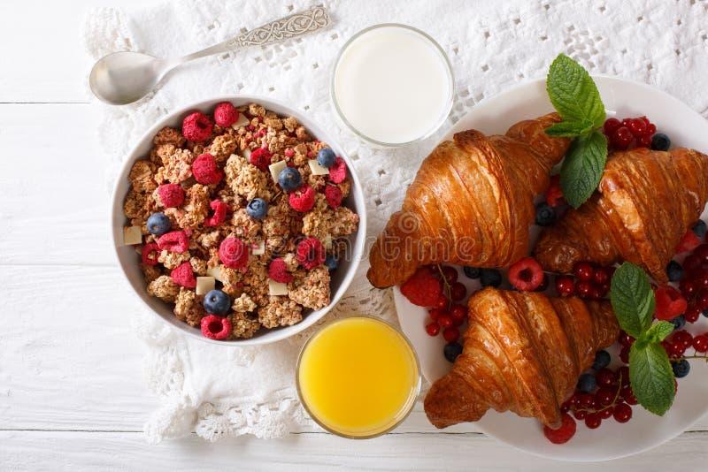 Muesli con le bacche e la fine dei croissant, del latte e del succo d'arancia immagine stock