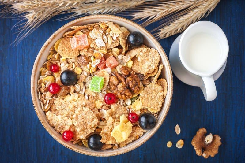 Muesli del cereale (granola) in una ciotola con le bacche e frutta secca e latte in una brocca. fotografia stock libera da diritti