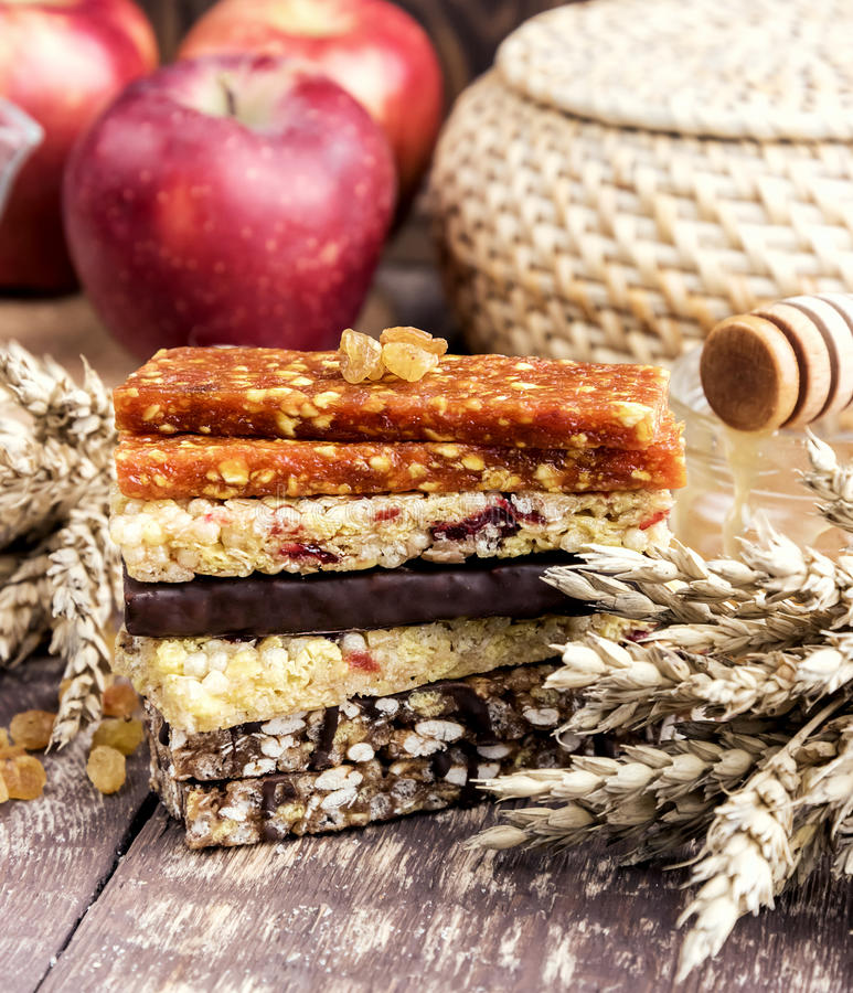 Muesli and dried fruit bars. Granola Dried apricot bars Apple Wooden background royalty free stock image