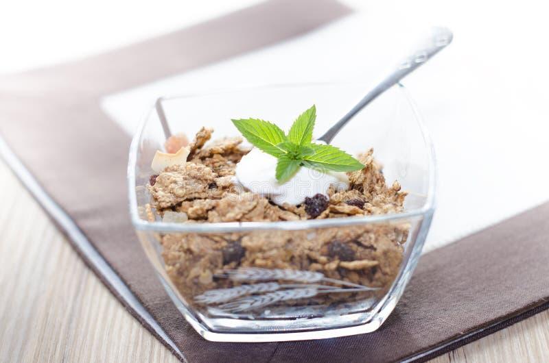 Muesli en un cuenco con el yogur, la menta y la fruta fresca imagen de archivo libre de regalías