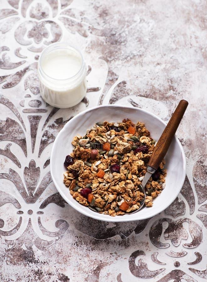 Muesli friável do granola com frutos secados, porcas e sementes e um frasco do iogurte fotos de stock