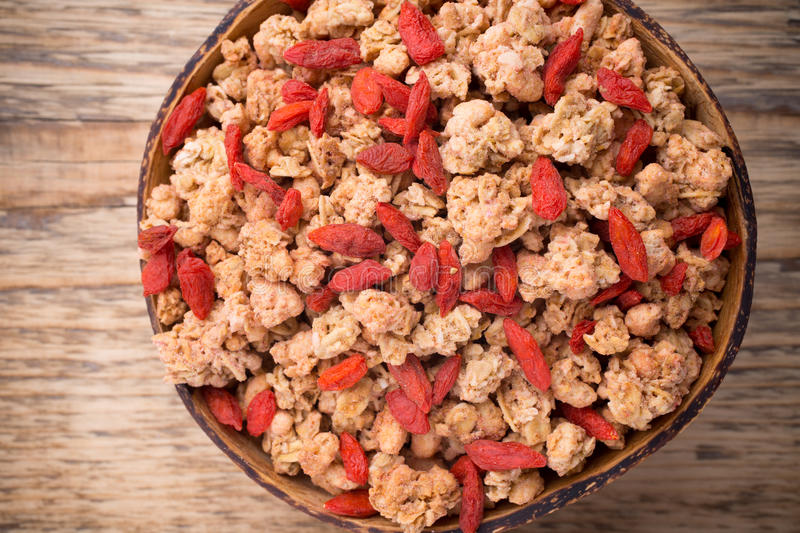 Muesli. Muesli with goji berries in a bowl on a wooden background stock images