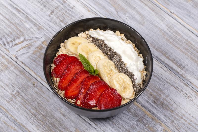 Muesli made from red strawberries, banana, chia seeds, oat flakes, honey and dressed with yogurt, close up royalty free stock photography