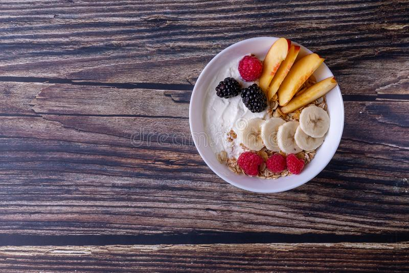Muesli met yoghurt en fruit op een donkere houten lijst stock foto