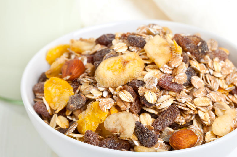 Muesli with milk. Muesli in bowl with bottle of milk in the background royalty free stock photography