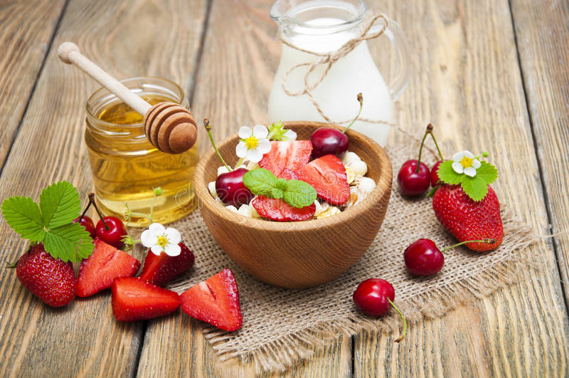 Muesli. Morning breakfast - muesli with fresh strawberries, cherries, honey and milk on a wooden table royalty free stock photos