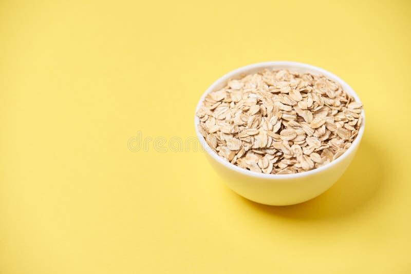 Muesli para la comida sana del desayuno Fondo amarillo Tazón de fuente blanco fotos de archivo