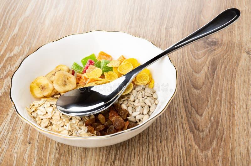 Muesli a séché des fruits, flocons d'avoine, farine d'avoine, graines de tournesol, les puces de banane, cuillère dans la cuve images stock