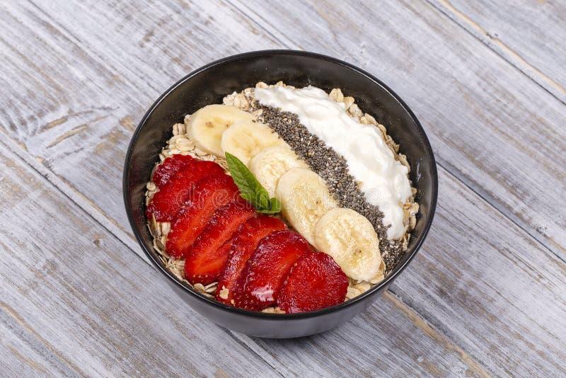 Muesli van rode aardbeien, banaan, chiazaden, haver wordt schilfert, honing gemaakt af en gekleed met yoghurt die, sluit omhoog royalty-vrije stock fotografie