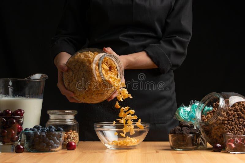 Muesli wird für die Zubereitung der gesunden und gesunden Nahrung des Frühstücks, Vegetarismus, auf einem schwarzen Hintergrund g lizenzfreies stockbild