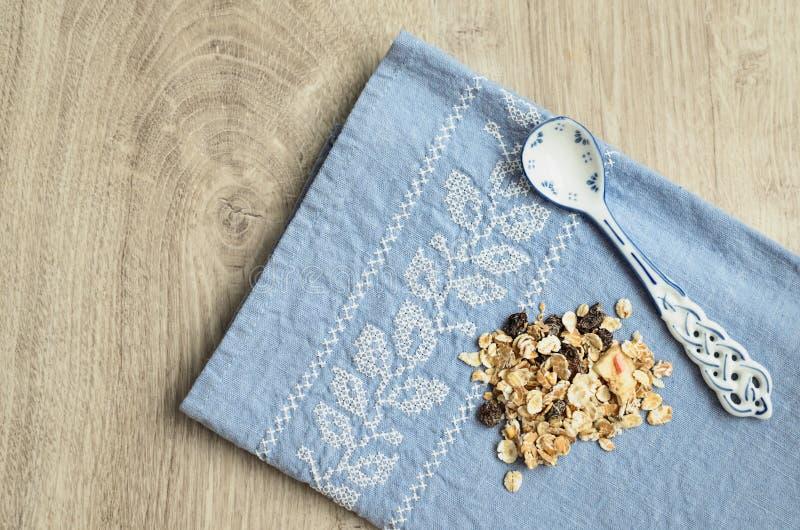 Muesli y cuchara con un modelo azul en el fondo de un mantel azul con bordado en un fondo de madera foto de archivo
