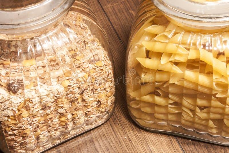 Muesli y pastas del penne en potes de los glas foto de archivo