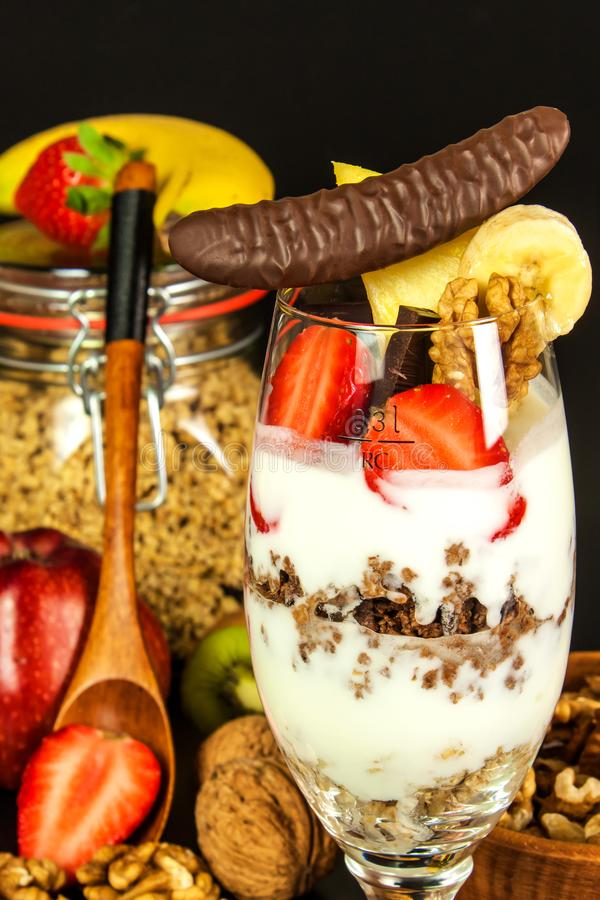 Muesli with yoghurt. Healthy food background with homemade oatmeal granola or muesli with nuts.  Muesli on a black table. Food for royalty free stock photo