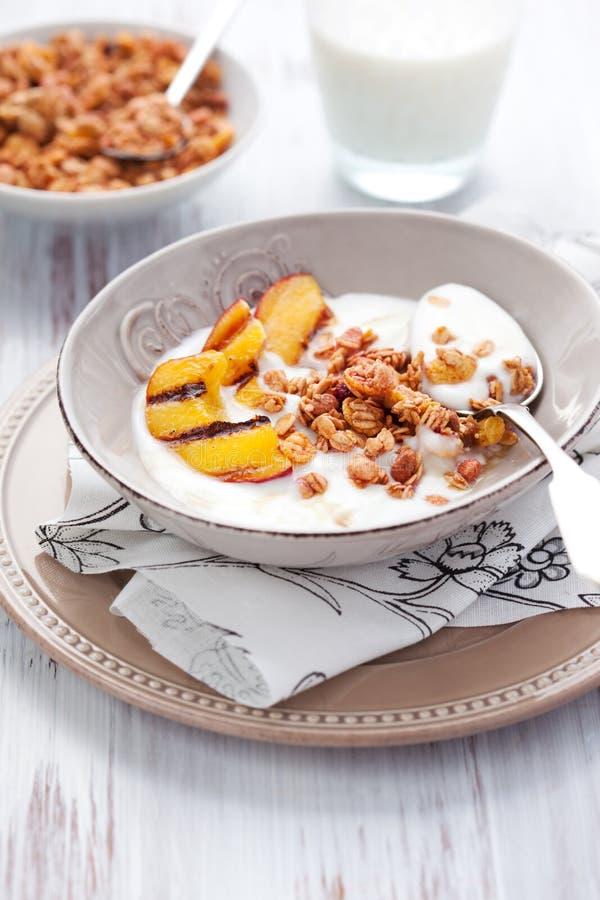 Muesli, yogurt e pêssegos grelhados fotografia de stock royalty free