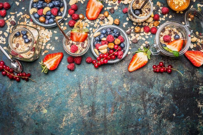 Muesli z świeżymi jagodami, dokrętkami i ziarnami, Zrównoważeni śniadaniowi składniki na nieociosanym tle zdjęcia stock