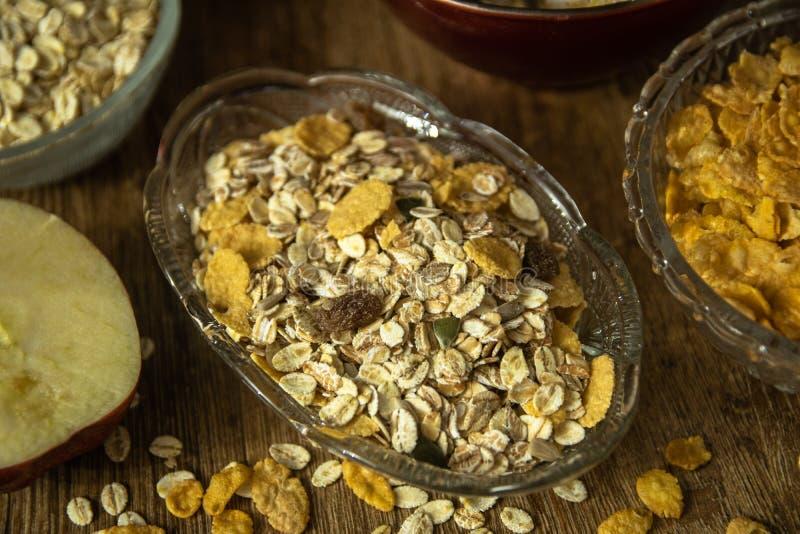 Muesli z wysuszonym - owoc, Jęczmienny płatek, świeży organicznie czerwony jabłko i kukurydzani płatki, zdjęcie stock