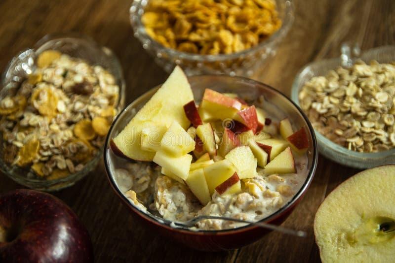 Muesli z wysuszonym - owoc, mleko i pokrojony czerwony jabłko na drewnianym stole, obraz stock
