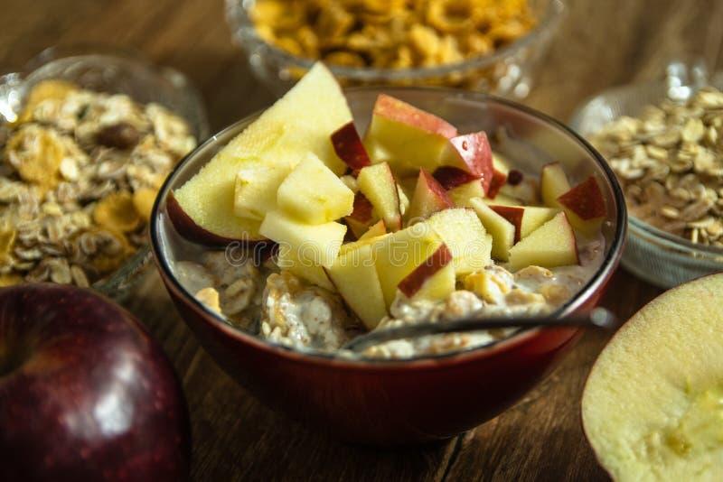 Muesli z wysuszonym - owoc, mleko i pokrojony czerwony jabłko na drewnianym stole, fotografia stock