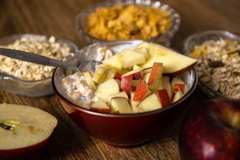 Muesli z wysuszonym - owoc, mleko i pokrojony czerwony jabłko na drewnianym stole, zdjęcie royalty free