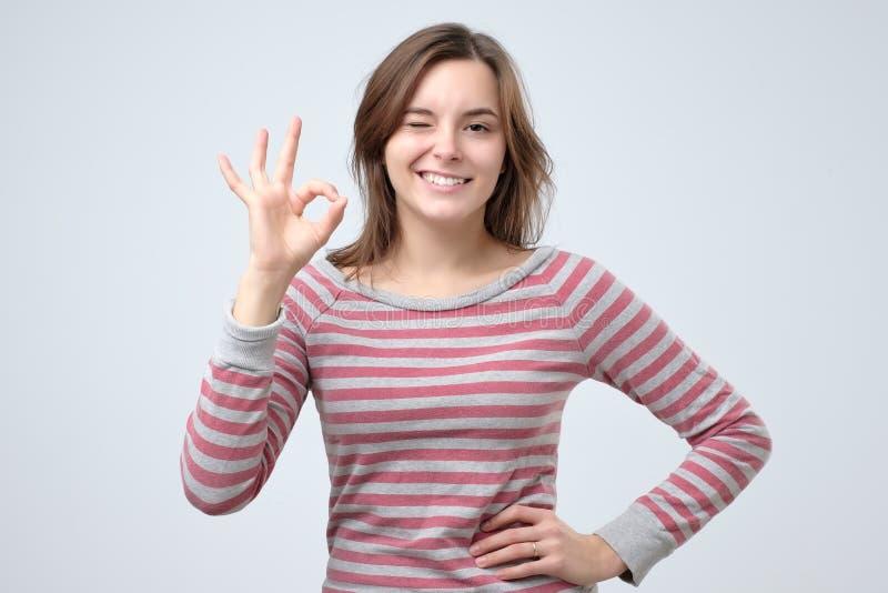 Muestra ACEPTABLE de la demostración europea joven hermosa de la mujer Ella está apoyando su opción imagen de archivo libre de regalías
