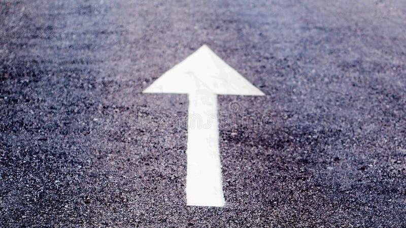 Muestra blanca en la carretera de asfalto, símbolo de la flecha del tráfico en la calle, fondo áspero superficial de la textura fotografía de archivo