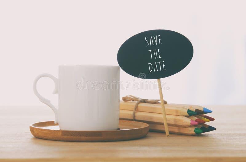 muestra con el texto: AHORRE LA FECHA al lado de la taza de café sobre la tabla de madera imagen de archivo