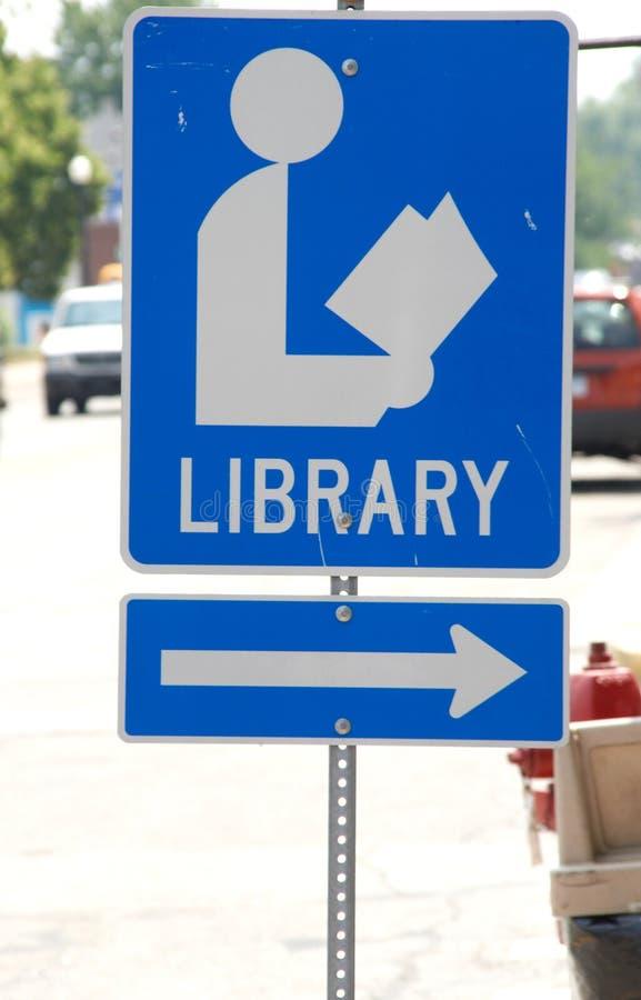 Muestra de biblioteca fijada adyacente a una calle con una flecha que señala a su destino imagen de archivo libre de regalías