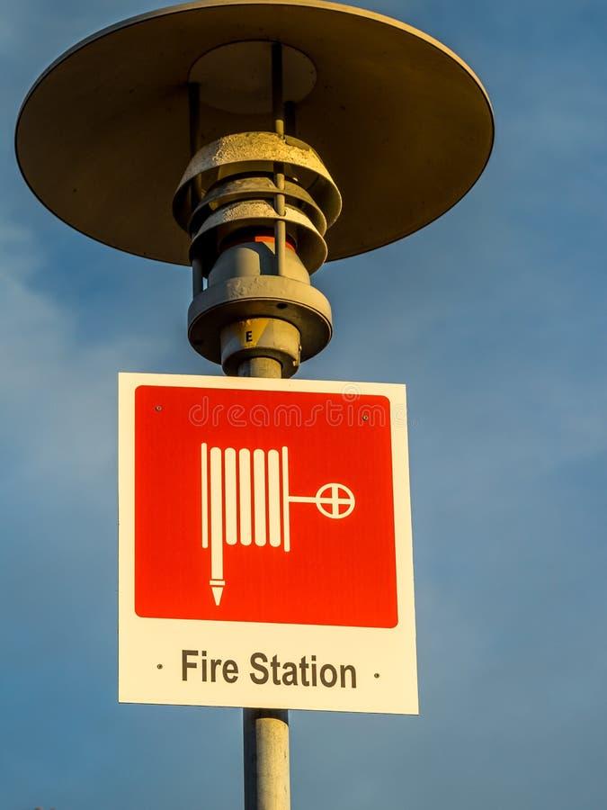 Muestra de la muestra del parque de bomberos, roja y blanca en un fondo del cielo azul de los posts de la lámpara fotografía de archivo libre de regalías