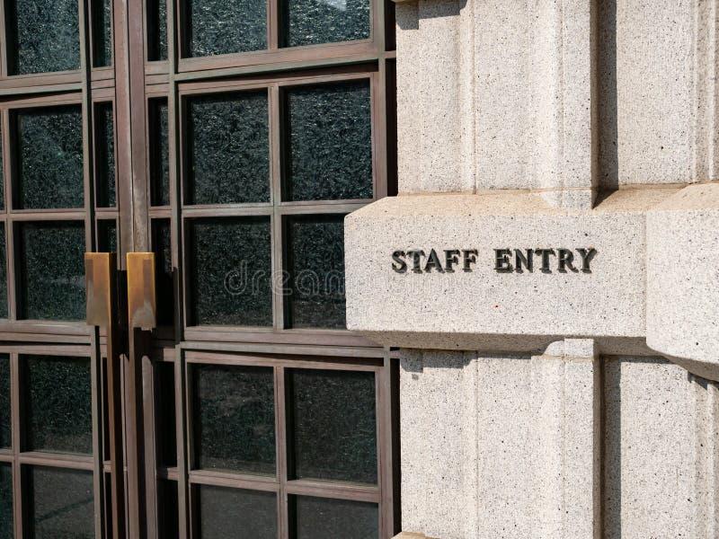 Muestra de la entrada del personal fuera del edificio de oficinas al lado de puertas dobles imágenes de archivo libres de regalías