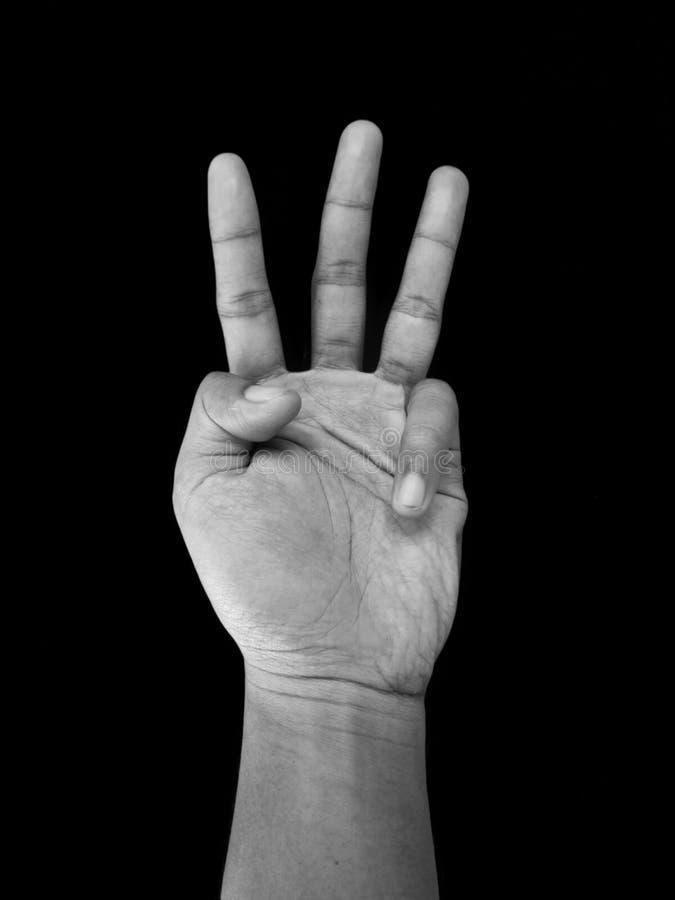 Muestra de la mano del número tres, aislada en fondo negro fotos de archivo