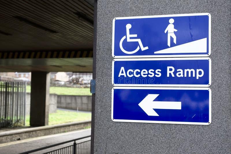 Muestra de la rampa de acceso para la silla de ruedas y la flecha discapacitada de la dirección de la ruta fotos de archivo