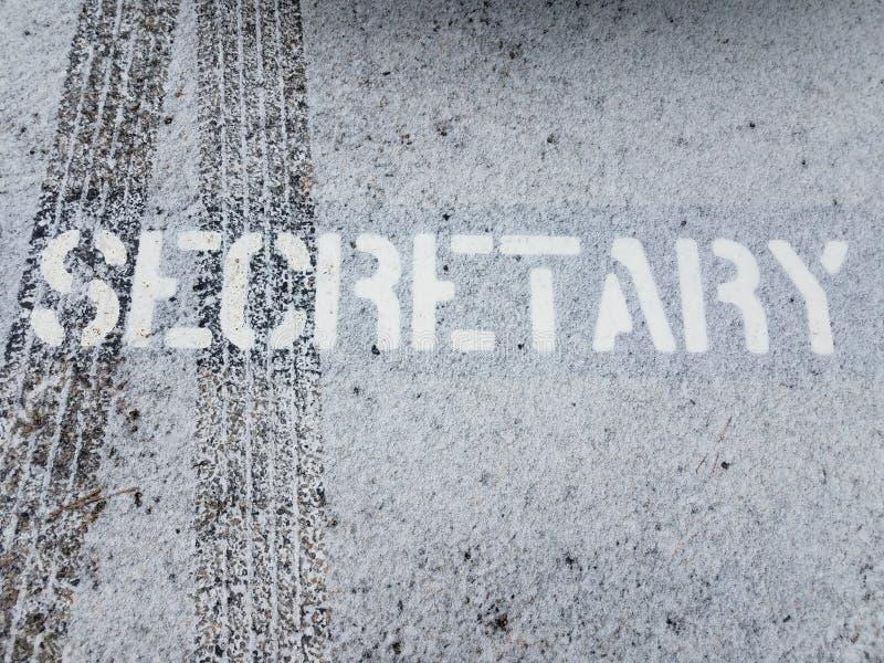 Muestra de la secretaria en el asfalto negro con las pistas del neumático y la nieve blanca fotografía de archivo libre de regalías
