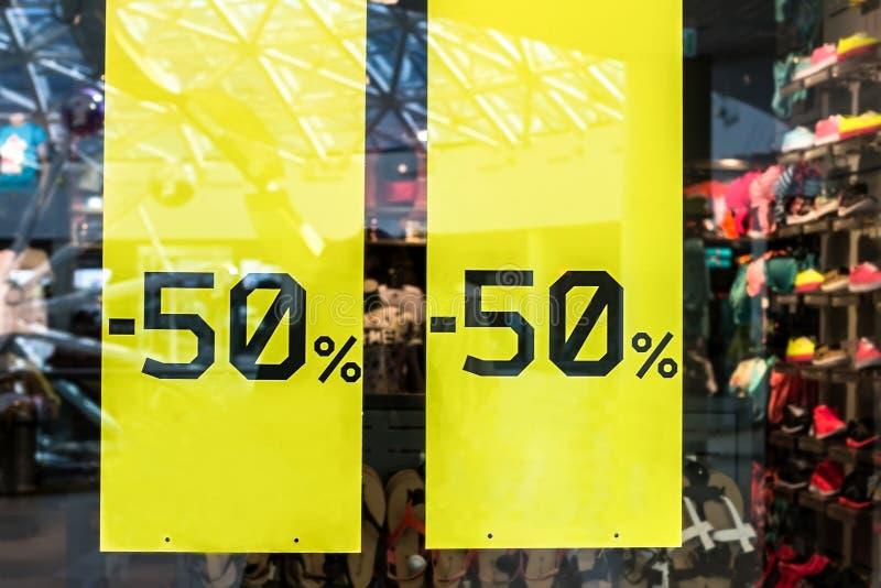 Muestra de la venta en tienda del paño Etiqueta engomada - hasta ventana a mitad de precio del 50 por ciento con ropa durante la  imagen de archivo libre de regalías