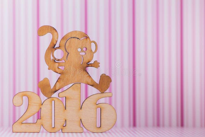Muestra de madera del mono y de la inscripción de 2016 años en tira rosada imágenes de archivo libres de regalías
