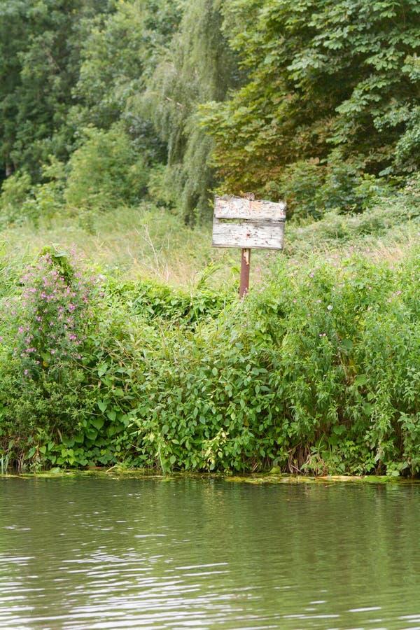 Muestra de madera descolorada del agua profunda del peligro en la orilla del río imagen de archivo libre de regalías