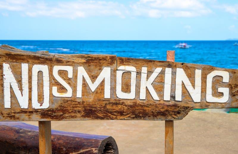 Muestra de no fumadores en la madera de deriva por el mar Prohibición del humo en la playa tropical Ambiente limpio de la playa imagen de archivo