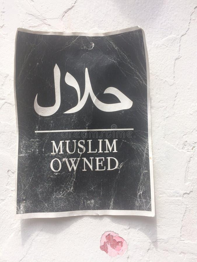 Muestra de papel con el texto y el x22; Owned& musulmán x22; colgante en una pared en Haji Lane en Singapur fotografía de archivo
