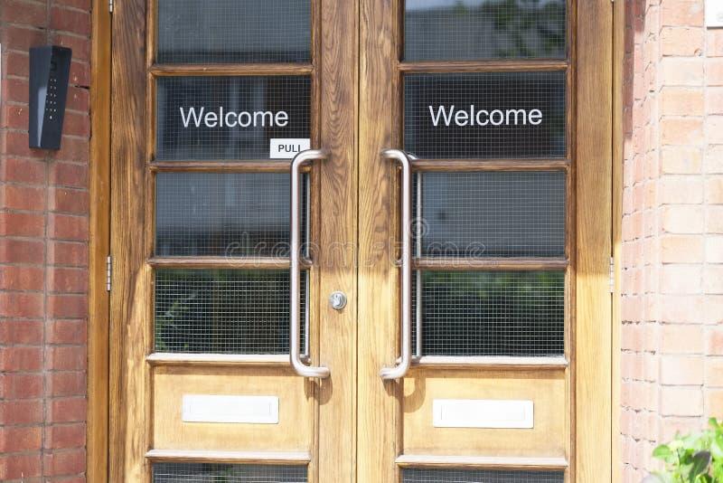 Muestra de saludo agradable de la entrada en puertas esmaltadas de madera dobles en el lugar de trabajo de oficina imagenes de archivo