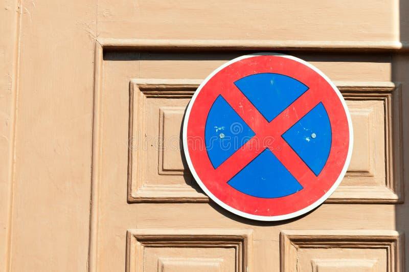 Muestra del estacionamiento prohibido en la puerta de madera de proteger la entrada contra los conductores de coche imagen de archivo