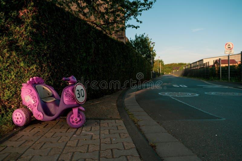 Muestra del límite de velocidad de 30 bajo la forma de paseo de los niños rosados en el vehículo foto de archivo libre de regalías