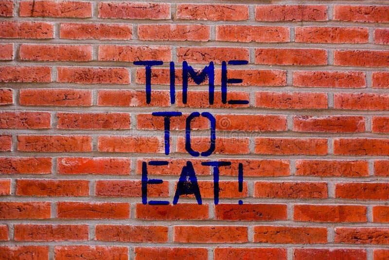 Muestra del texto que muestra hora de comer Momento correcto de la foto conceptual para gozar de una pared de ladrillo que muere  imágenes de archivo libres de regalías