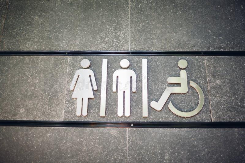 Muestra del WC de los retretes p?blicos en la pared al aire libre Para la hembra, el var?n y las personas discapacitadas foto de archivo