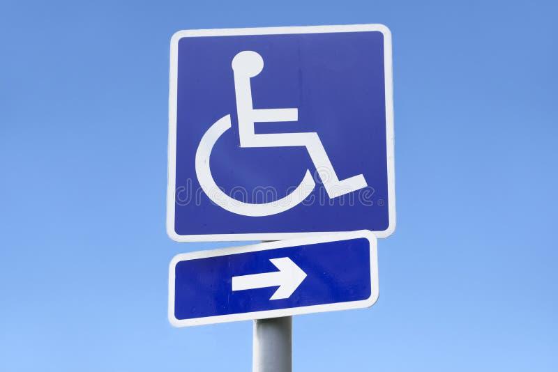 Muestra discapacitada de la silla de ruedas y de la flecha de la dirección contra el cielo azul claro vacío foto de archivo libre de regalías