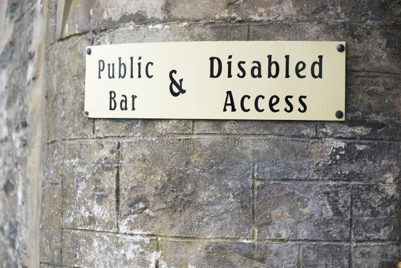 Muestra discapacitada del acceso en la pared de piedra en la entrada del pub de la barra pública fotos de archivo