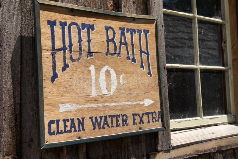 Muestra divertida para un suplemento del agua potable del baño caliente para 10 centavos en un edificio abandonado de madera rúst foto de archivo