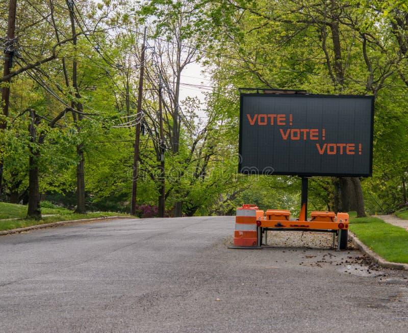 Muestra eléctrica del LED en el remolque que dice el voto, voto, voto en una calle suburbana alineada con los árboles imagen de archivo libre de regalías