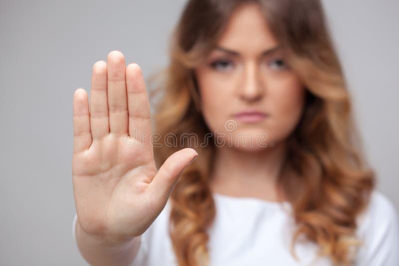 Muestra femenina de la parada de la mano foto de archivo
