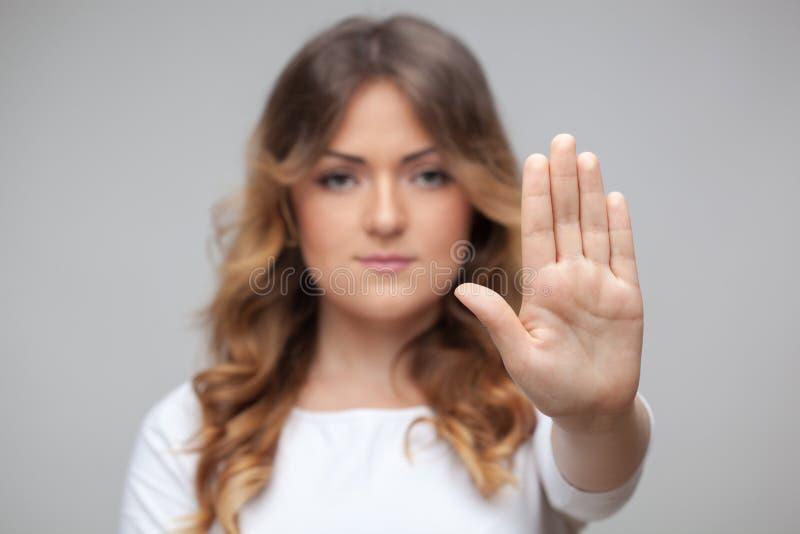 Muestra femenina de la parada de la mano aislada en blanco fotos de archivo libres de regalías
